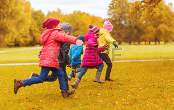 49277163-autumn-childhood-leisure-and-people-concept--group-of-happy-little-kids-playing-tag-game-and-running